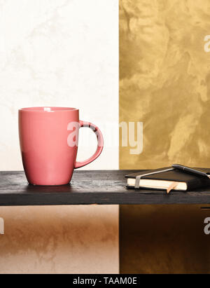 pink tea or coffee cup or ceramic mug for drink copybook and pen black tray on brown and beige textured background, copy space - Stock Photo