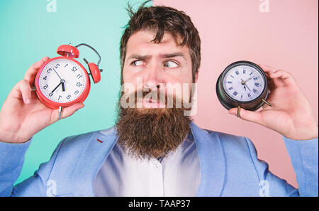 Guy unshaven puzzled face having problems with changing time. Changing time zones affect health. Time zone. Does changing clock mess with your health. Man bearded hipster hold two different clocks. - Stock Photo