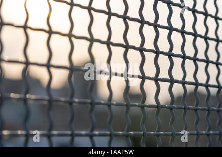 Close-up of a small mesh metal fence, with a blurry bokeh background of some Manhattan buildings - Stock Photo