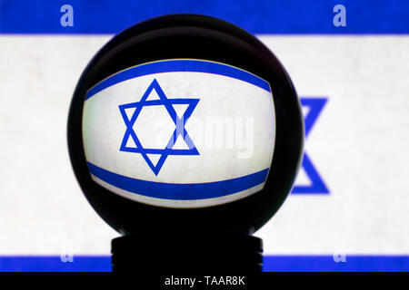 Flag of Israel in reflection on a crystal ball against a blurred Israeli flag - Stock Photo