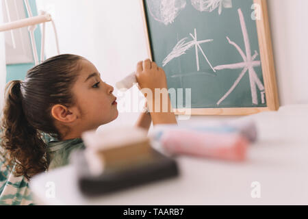 little girl concentrated drawing with a chalk on the blackboard at her room at home, copy space for text - Stock Photo