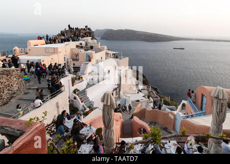 Santorini, Greece - May 7 2019: A large crowd of tourists gather at the famous viewpoint in Oia to check the sunset over the iconic village in Santori - Stock Photo