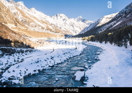 The cold and calm Baspa River flowing towards the Sangla valley through the snow-clad mountains and Chitkul, Himachal Pradesh. - Stock Photo