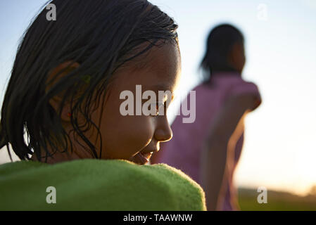 Side profile of a beautiful young Asian girl wrapped in a towel after having a cold shower outdoors during a camping trip - Stock Photo