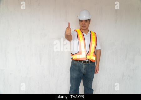 Asian professional engineer workering in house construction site for inspection of the cottage under construction and lift the thumb up. - Stock Photo