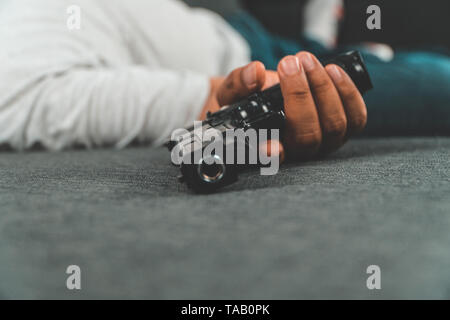 Middle-aged Asian man 40 years old hold gun in his hand and lying on the sofa in his house. Simulate the situation of people who have stress from work - Stock Photo