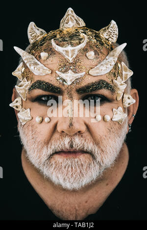 Man with dragon skin and white beard. Monster with sharp thorns and warts on face, horror and fantasy concept. Demon head on black background - Stock Photo