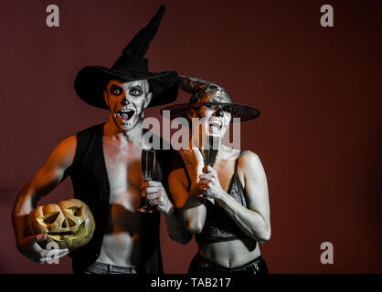 Halloween woman and man has happy face in witch hat. - Stock Photo