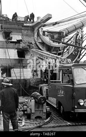 AJAXNETPHOTO. 27TH FEBRUARY, 1973. PORTSMOUTH,ENGLAND - FIRE IN THE HOLE! - MEMBERS OF PORTSMOUTH CITY FIRE BRIGADE STRUGGLE TO PUT OUT A FIRE IN ADMIRAL HORATIO NELSON'S FAMOUS TRAFALGAR FLAGSHIP H.M.S. VICTORY, STARTED WHILE RESTORERS WERE REMOVING OLD PAINT FROM INSIDE THE BOW SECTION. 