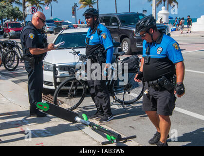 Ft Lauderdale, Florida - May 4, 2019: Police officers investigate an electric motor scooter accident on the street by the beach on this date - Stock Photo