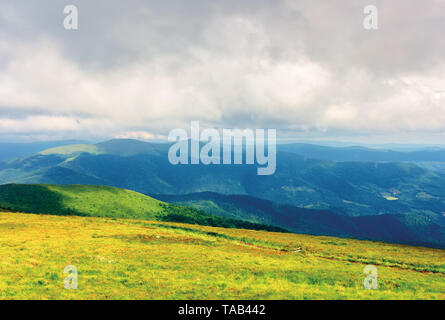 mountain landscape on a cloudy day. footpath through grassy meadow. mountain ridge in the distance. stormy weather in summer - Stock Photo