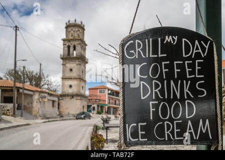 Zakynthos, Greece -  April 2019 : Black cafe board advertising food, coffee, drinks and ice cream with church tower in the background, Agios Leon vill - Stock Photo