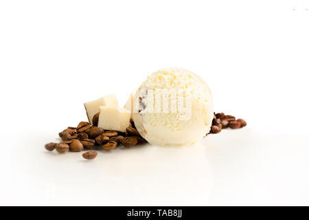 Ice cream ball, coffee and creme souffle flavor with ingredients, coffee beans and slices of souffle, isolated on a white background. - Stock Photo