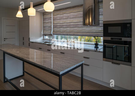 Modern kitchen furniture with marble worktops , drawers, cabinets, faucet by a kitchen sink, hob, steam collector, oven, electrical sockets. - Stock Photo