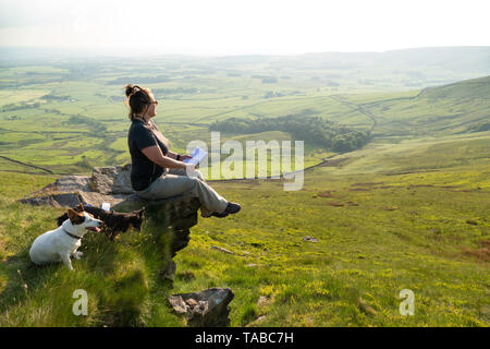 Woman outdoors enjoying the fine views in the forest of bowland a.o.n.b. whilst sitting on a rocky outcrop known as 'Nick's chair' - Stock Photo
