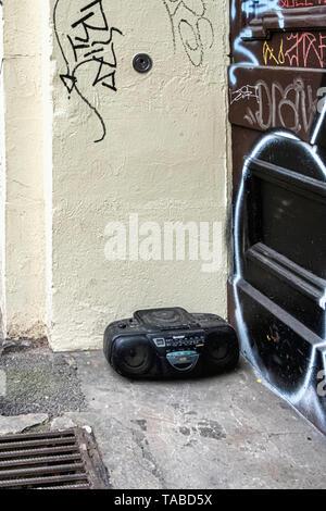 Old technology - Abandoned, dumped, trashed. Redundant radio & CD player dumped on a city pavement. - Stock Photo