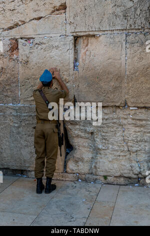 Jewish man prays next to a crack filled with letters containing written prayers at the Western Wall in Jerusalem. Israel - Stock Photo