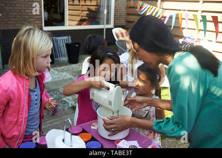 A group of young children having fun baking cup cakes outside in the back garden during a birthday party - Stock Photo