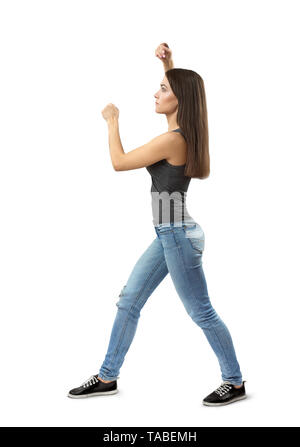 Side view of young woman in gray top and blue jeans standing, fist before face. other arm above head, right foot forward isolated on white background. - Stock Photo