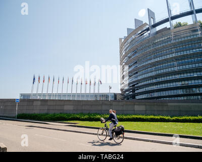 Strasbourg, France - May 23, 2019: Adult woman on bicycle with European Parliament headquarter building in background all EU members states flags waving