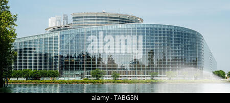 Wide facade of European Parliament headquarter in Strasbourg a day before 2019 European Parliament election - clear blue sky and calm Ill river water reflected in the glass facade. - Stock Photo