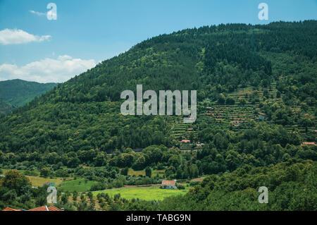 Countryside landscape with cottages on hill covered by cultivated fields at Manteigas. A genuine mountain village at Serra da Estrela in Portugal. - Stock Photo