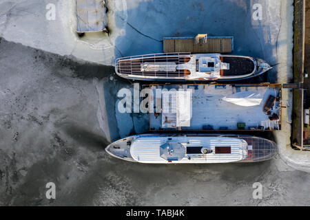 Aerial view of two ships frozen in a lake in winter on sunny day. - Stock Photo