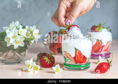 Woman hand holding cream strawberry. Glass bowl of strawberries with whipped cream and mint. Jasmine flowers. Concrete surface, copy space  for you te - Stock Photo