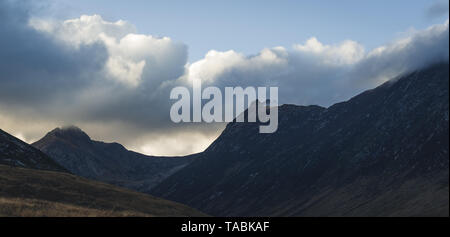 Landscape shot of a rugged mountain range against an unsettled sky. - Stock Photo