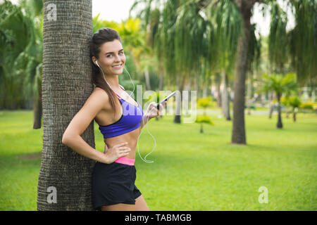 Fitness woman in earphones listening music during her workout in the park - Stock Photo