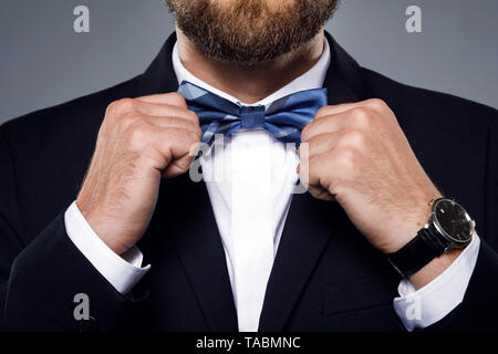 Man is fiting up a beautiful bow tie for evening - Stock Photo