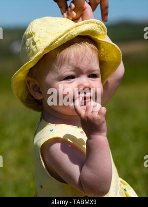 Baby girl in a yellow dress. - Stock Photo
