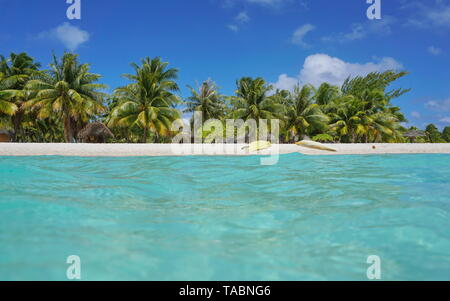 Tropical sea shore with kayaks on the beach and coconut trees with huts, seen from water surface, atoll of Tikehau, Tuamotu, French Polynesia, Pacific - Stock Photo