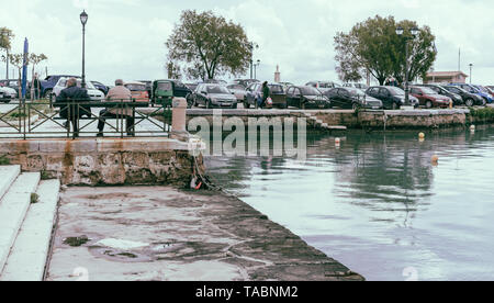 Zakynthos, Greece -  April 2019 : Two older man sitting on a bench in Zakynthos Port - Stock Photo