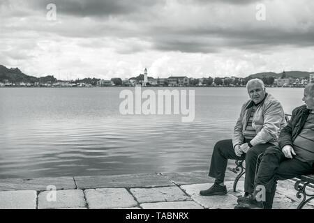 Zakynthos, Greece -  April 2019 : Two older man sitting on a bench in Zakynthos Port, Greece - Stock Photo
