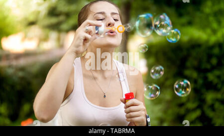 Portrait of happy smiling young woman blowing colorful soap bubbles at summer park - Stock Photo