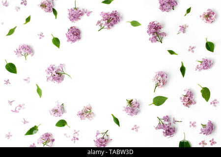 frame with leaves and lilac petals on white background. flat lay, overhead view