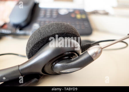 Headset with telephone in the background in the office on the desk - Stock Photo