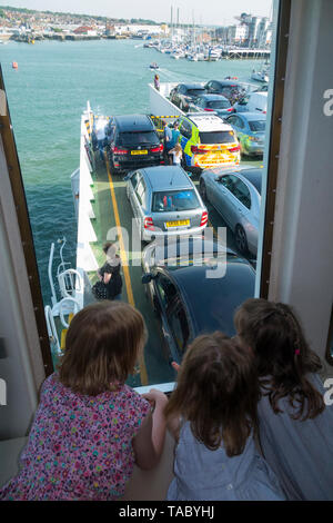 Child / kids / passengers on a Red Funnel ferry between UK mainland - Southampton - & Cowes on the Isle of Wight look out of the window and down onto the car deck. UK. (99) - Stock Photo