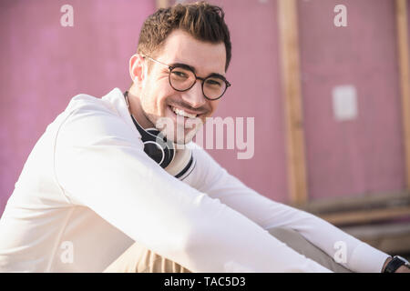 Portrait of happy young man in front of pink wall - Stock Photo