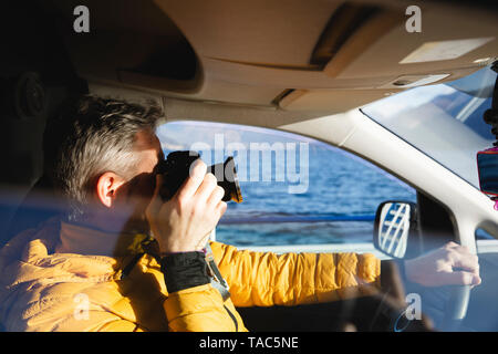 Italy, Como, man taking picture from the car - Stock Photo
