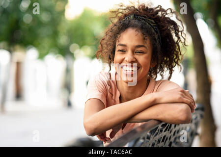 Portrait of happy young woman sitting on a bench Stock Photo