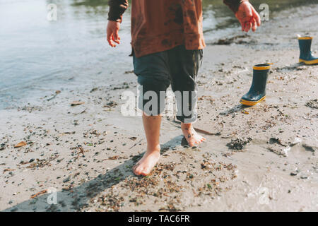 Boy playing on a the beach, walking barefoot in the mud Stock Photo