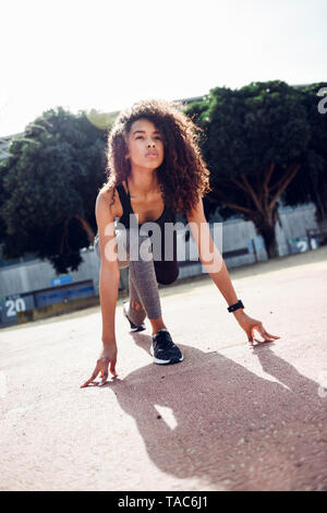 Sporty young woman on tartan track starting - Stock Photo