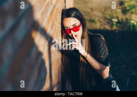 Spain, portrait of a teenage girl with finger on mouth - Stock Photo