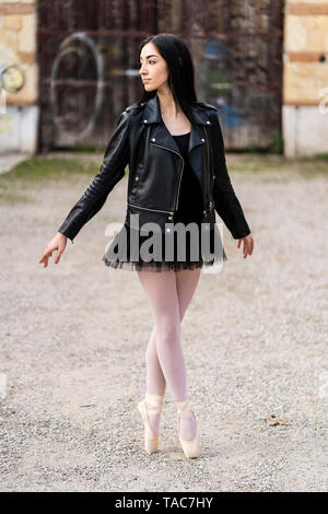 Italy, Verona, Ballerina dancing in the city wearing leather jacket and tutu - Stock Photo