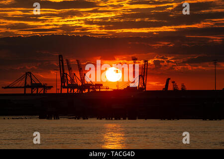 Gravesend, Kent, United Kingdom. 23rd May, 2019. Dramatic sunset over the River Thames seen from Gravesend looking towards Tilbury Docks. Rob Powell/Alamy Live News - Stock Photo