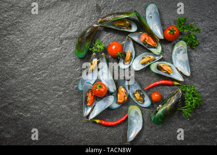 Shell  Mussel cooking seafood plate with Shellfish green mussels ocean gourmet dinner cooked with herbs and spices on dark stone background top view - Stock Photo