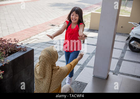 daughter running and hugging mum - Stock Photo