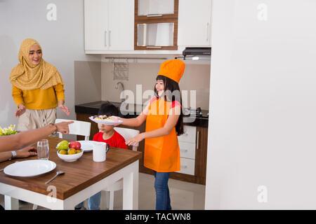 daughter help mom preparing food - Stock Photo